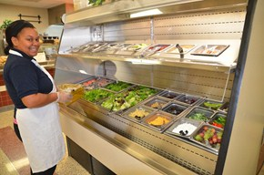 An employee oversees the salad bar at one of our school cafeterias.