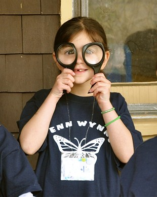 Penn Wynne student holding magnifying glasses up to her eyes like a pair of glasses.